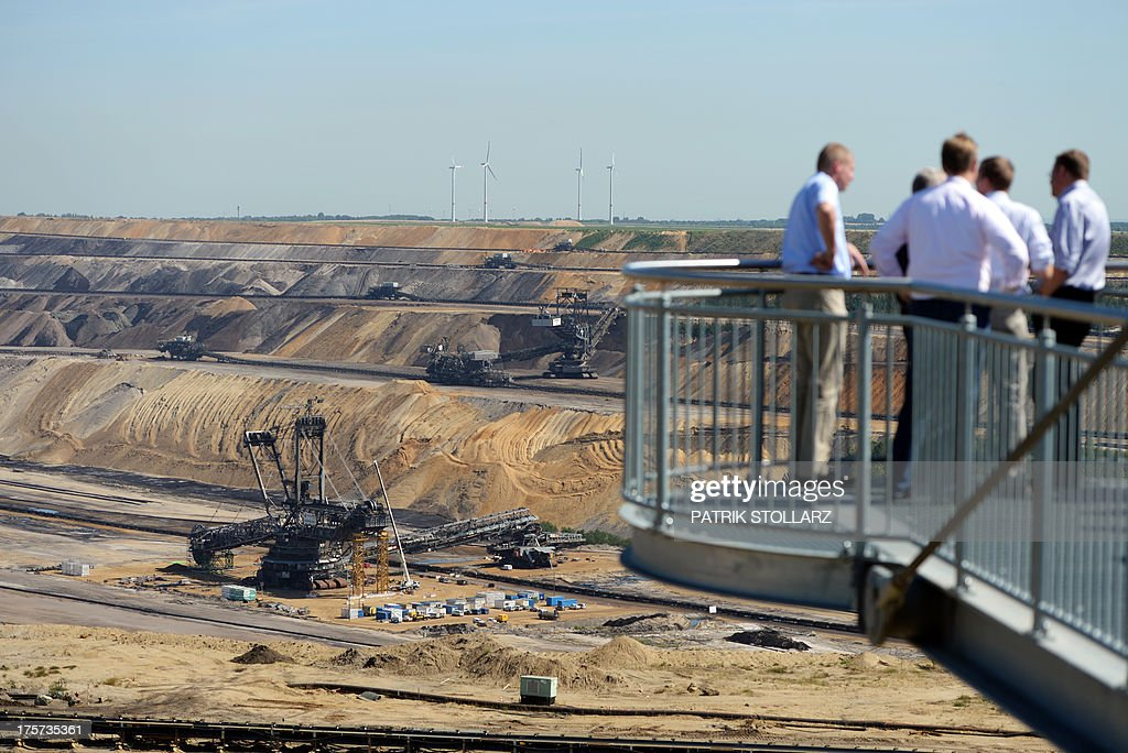 People stand on a platform at the brown coal open cast mine Garzweiler on August 5, 2013 in Immigrath, western Germany. The small town Immerath and surrounding towns will be wiped off the map to allow energy giant RWE enlarge the huge open pit mine Garzweiler.