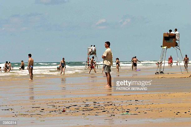 People stand on a polluted Biscarosse beach southwestern France 05 July 2003 hit by oil remains seven months after the sinking of the Prestige oil...