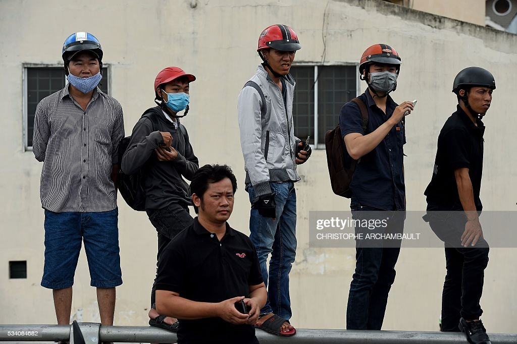 People stand on a railing as they line up the streets to catch a glimpse of US President Barack Obama on his way to the airport at the end of two-day visit to Ho Chi Minh City on May 25, 2016. Obama fielded questions on May 25 on everything from rap and weed smoking to leadership and his good looks at a lively town hall-style meeting with young Vietnamese, who say the US leader is a far cry from their staid Communist rulers. / AFP / CHRISTOPHE