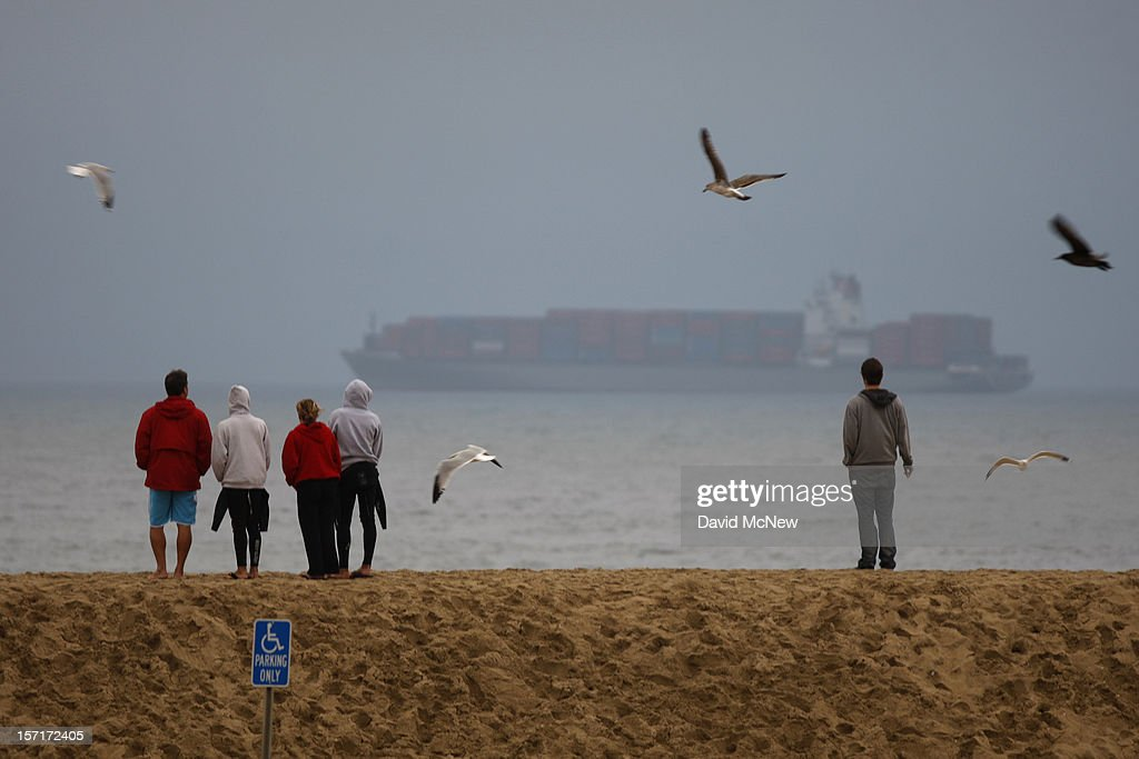 People stand on a sand berm with a view of anchored container ships which cannot enter the ports of Los Angeles and Long Beach to load and unload cargo because of a strike by the International Longshore and Warehouse Union Local on November 29, 2012 in Seal Beach, California. The strike is the largest work stoppage at the ports of Los Angeles and Long Beach since a lockout by shipping companies in 2002, which prompted President George W. Bush to intervene with a court injunction to resolve the standoff.