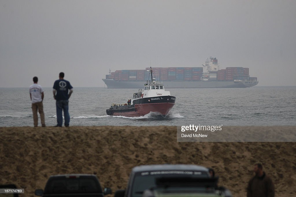 People stand on a sand berm with a view of anchored container ships which cannot enter the ports of Los Angeles and Long Beach to load and unload cargo because of a strike by the International Longshore and Warehouse Union Local on November 29, 2012 in Seal Beach, California. The strike is the largest work stoppage at the ports since a lockout by shipping companies in 2002, which prompted President George W. Bush to intervene with a court injunction to resolve the standoff.