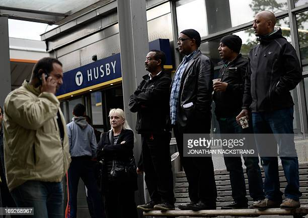 People stand on a street bench next to Husby subway station as they attend a demonstration against police violence and vandalism in the Stockholm...
