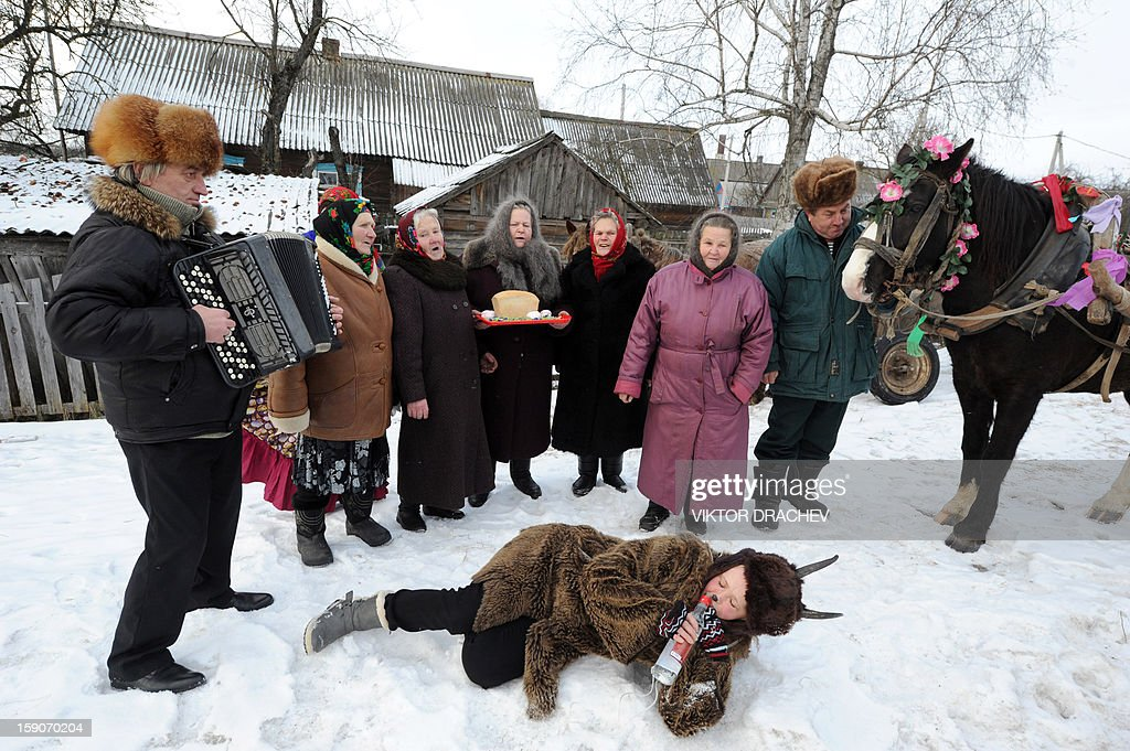 People stand on a street covered with snow as they attend Christmas celebrations in the town of Richev, some 290 km south from Minsk, on January 7, 2013. Orthodox Christians celebrate Christmas on January 7 in the Middle East, Russia and other Orthodox churches that use the old Julian calendar instead of the 17th-century Gregorian calendar adopted by Catholics, Protestants, Greek Orthodox and commonly used attendsin secular life around the world. AFP PHOTO / VIKTOR DRACHEV