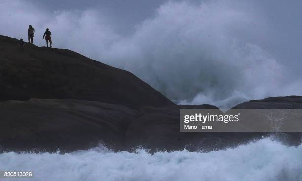 People stand on Arpoador rock during strong winter swells on the Atlantic Ocean on August 11 2017 in Rio de Janeiro Brazil Waves were measured as...