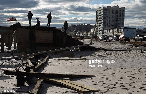 People stand on destroyed boardwalk debris from Superstorm Sandy at Rockaway Beach on November 3 2012 in the Queens borough of New York City Most of...