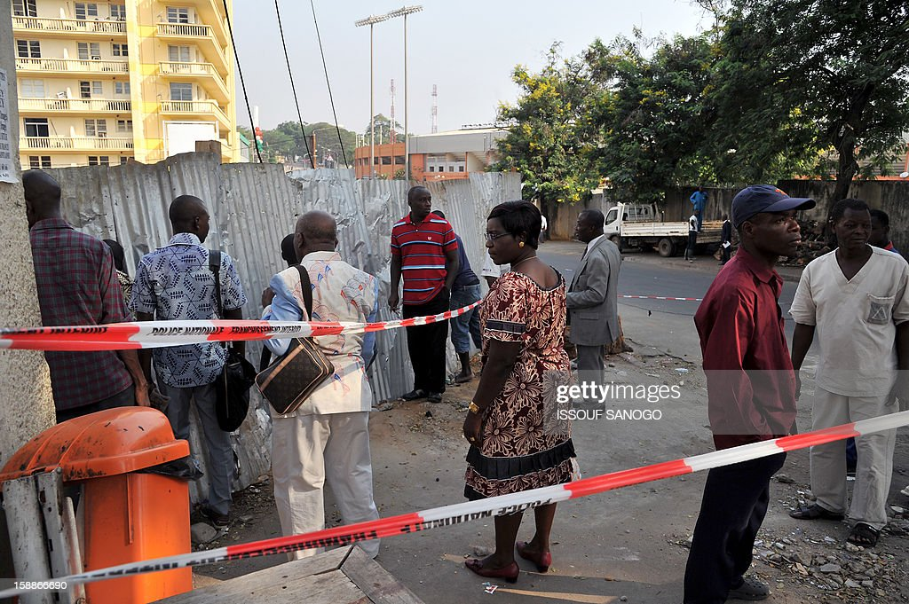 People stand on January 2, 2013 in a street of Abidjian where at least 60 persons died in a stampede among crowds gathered for celebratory New Year's Eve fireworks that also left dozens injured. Ivory Coast began today three days of national mourning.