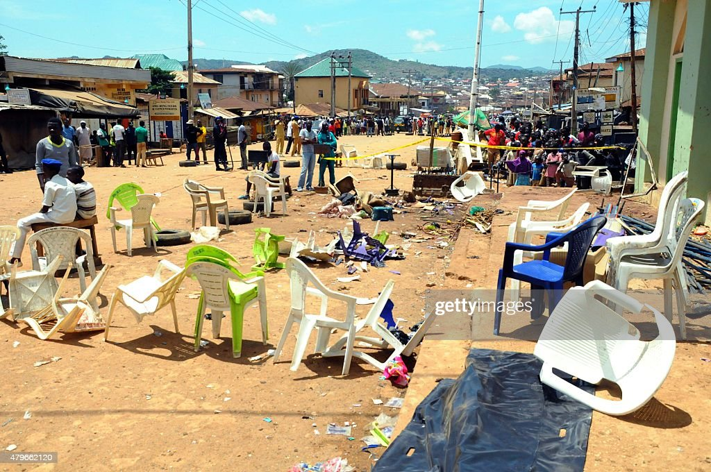 People stand on July 6, 2015 in the central Nigerian city of Jos, Plateau State, at the scene where a twin bomb blasts the day before killed at least 44 people, after a wave of mass casualty attacks blamed on Boko Haram militants. The blasts happened within minutes of each other at a shopping complex and near a mosque in the religiously divided capital of Plateau state, which the rebels have targeted before. The bombings took the death toll from raids, explosions and suicide attacks to 267 this month alone and to 524 since Muhammadu Buhari became president on May 29, according to an AFP count. AFP PHOTO
