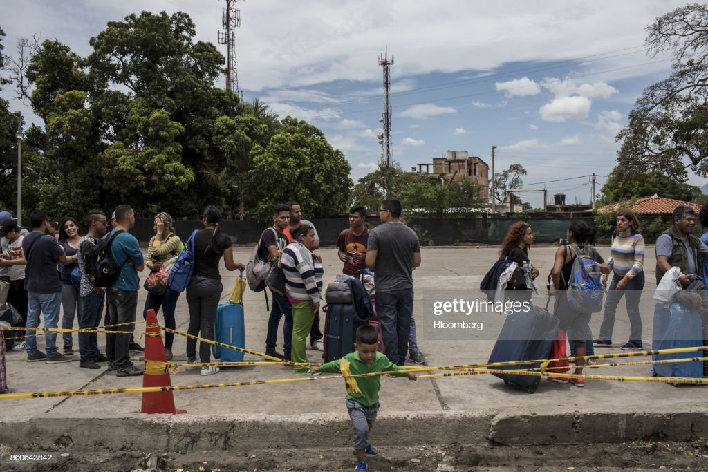 People stand on line outside the Immigration office in the town of Villa del Rosario, Cucuta, Colombia, on Thursday, Sept. 21, 2017. For weeks, Venezuelans have been flocking by the busload to San Antonio del Tachira, a border town of some 62,000 residents, fleeing as President Nicolas Maduro consolidates autocratic power. According to Colombia's migration authority, the number of foreigners entering Cucuta, the first major city across the bridge, more than doubled this summer. Photographer: Nicolo Filippo Rosso/Bloomberg via Getty Images