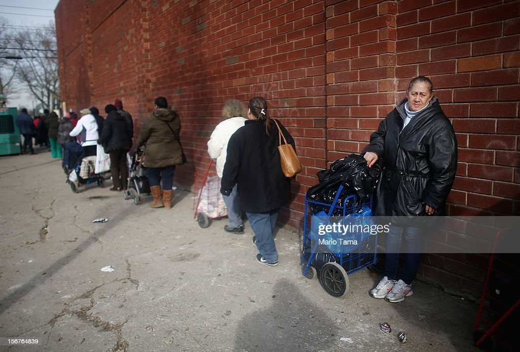 People stand on line to obtain food and other items from a distribution point in the Coney Island neighborhood on November 20, 2012 in the Brooklyn borough of New York City. The Coney Island area was hard hit by Superstorm Sandy.
