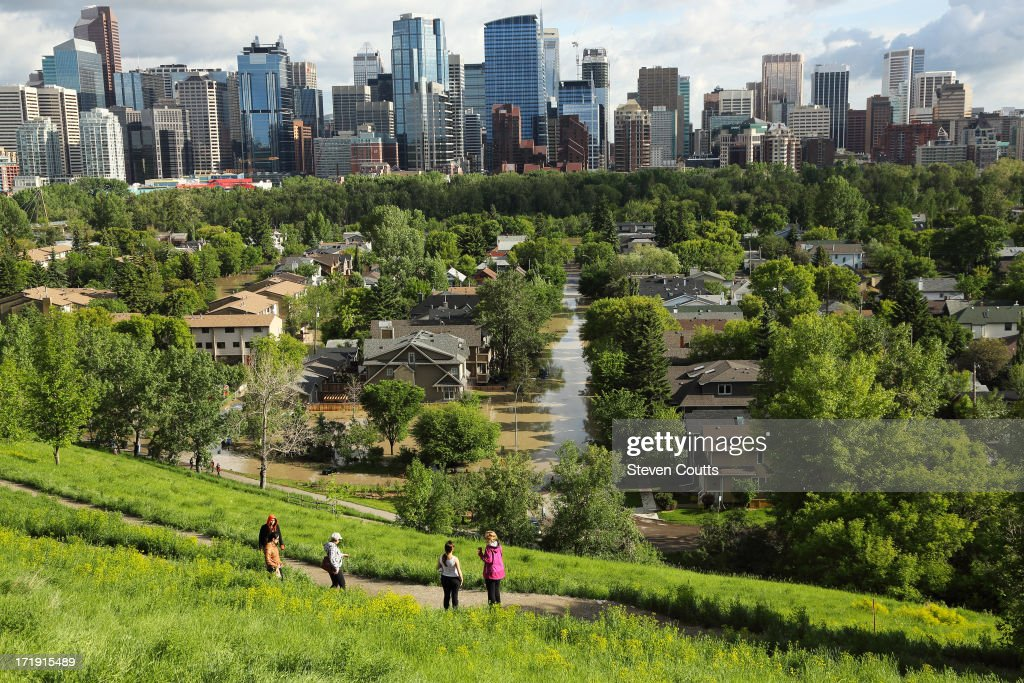 People stand on the banks of McHugh Bluff and survey the damage caused in the community of Sunnyside. The recent flooding was some of the worst in Calgary's history. Calgary's downtown core is seen in the background.