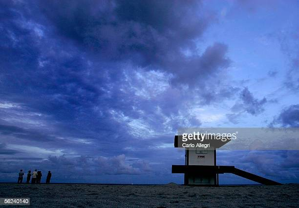 People stand on the beach and watch the sunset in the twilight November 19 2005 in Hollywood Florida Tropical Storm Gamma approaches South Florida as...