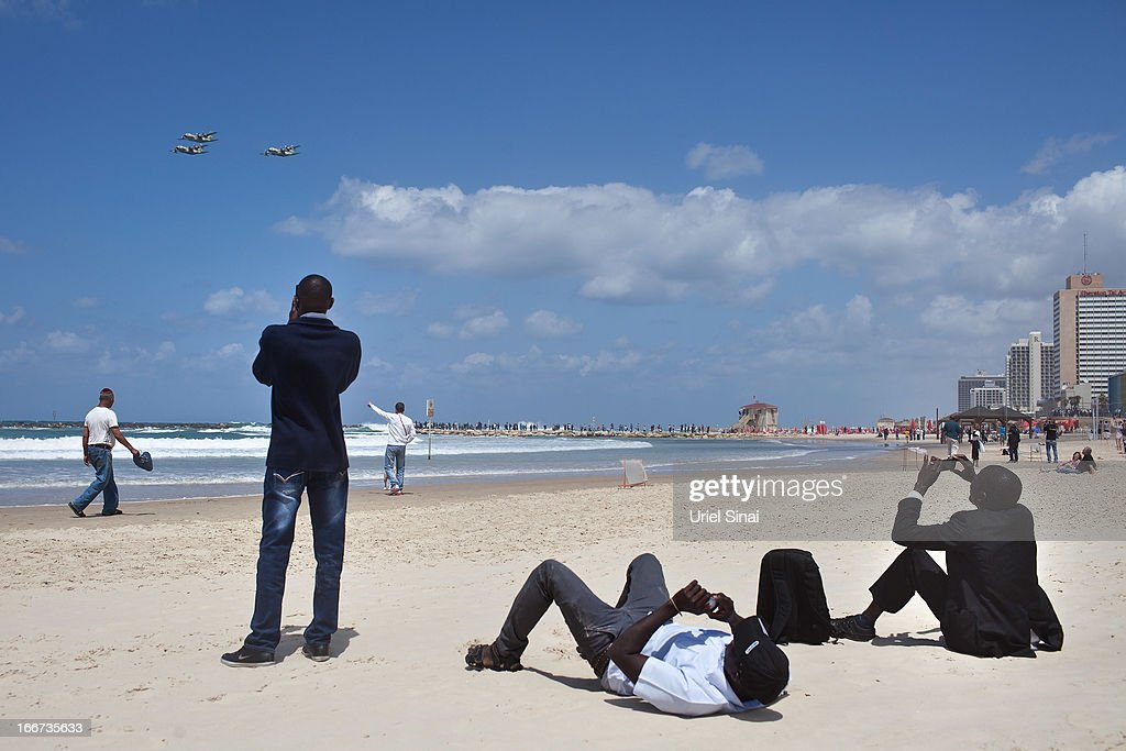 People stand on the beach in the Mediterranean sea as they watch a military air show marking the 65th anniversary of Israel's independence on April 16, 2013 in Tel Aviv, Israel. The day marks when David Ben-Gurion, the Executive Head of the World Zionist Organization declared the establishment of a Jewish state in Eretz- Israel.