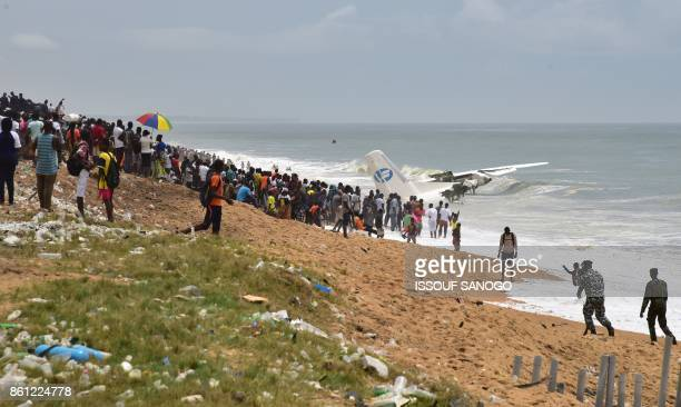 People stand on the beach of PortBouet in Abidjan as they look at the wreckage of a cargo plane that crashed off Ivory Coast killing four on October...