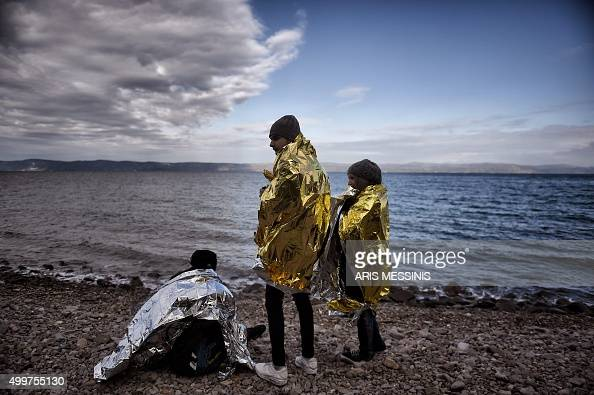 TOPSHOT People stand on the beach wrapped in emergency blankets after a group of refugees and migrants arrived on the Greek island of Lesbos on...