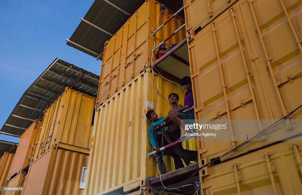 People stand on the corridor at a construction workers' camp on May 6, 2016 in Bangkok, Thailand. Mainly migrants from neighboring countries, like Cambodia and Laos, live in this camp, which has grocery shops, a common washing area and even a small school, on the outskirts of Bangkok.
