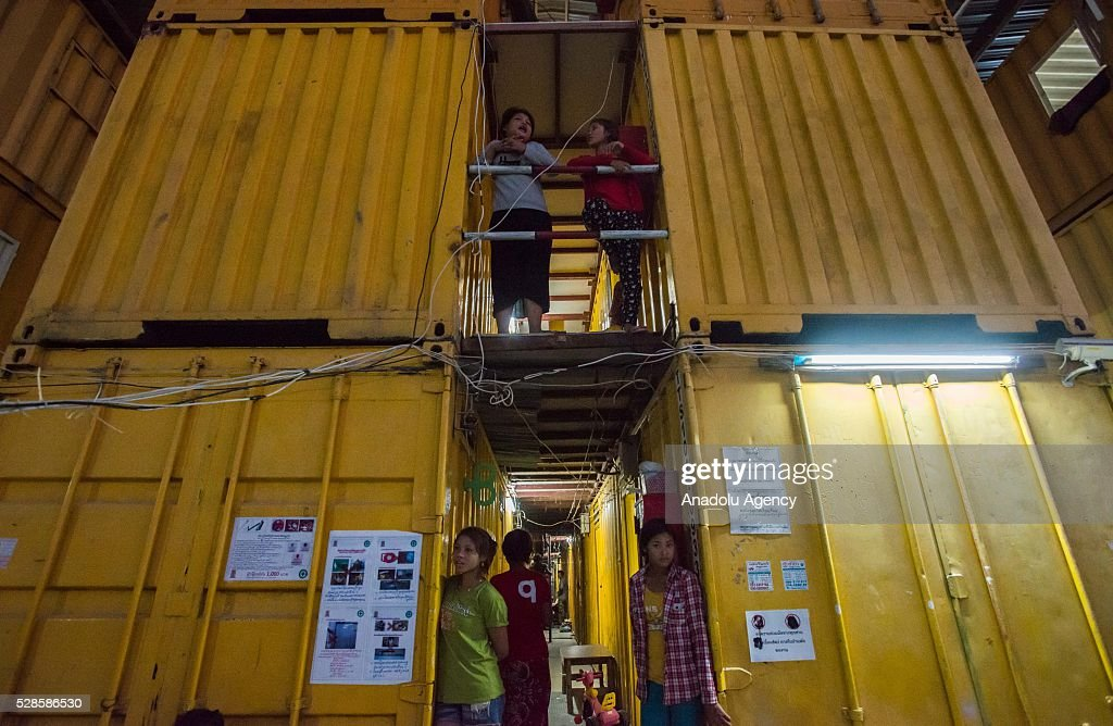People stand on the corridor at a construction workers' camp on May 6, 2016 in Bangkok,Thailand. Mainly migrants from neighboring countries, like Cambodia and Laos, live in this camp, which has grocery shops, a common washing area and even a small school, on the outskirts of Bangkok.