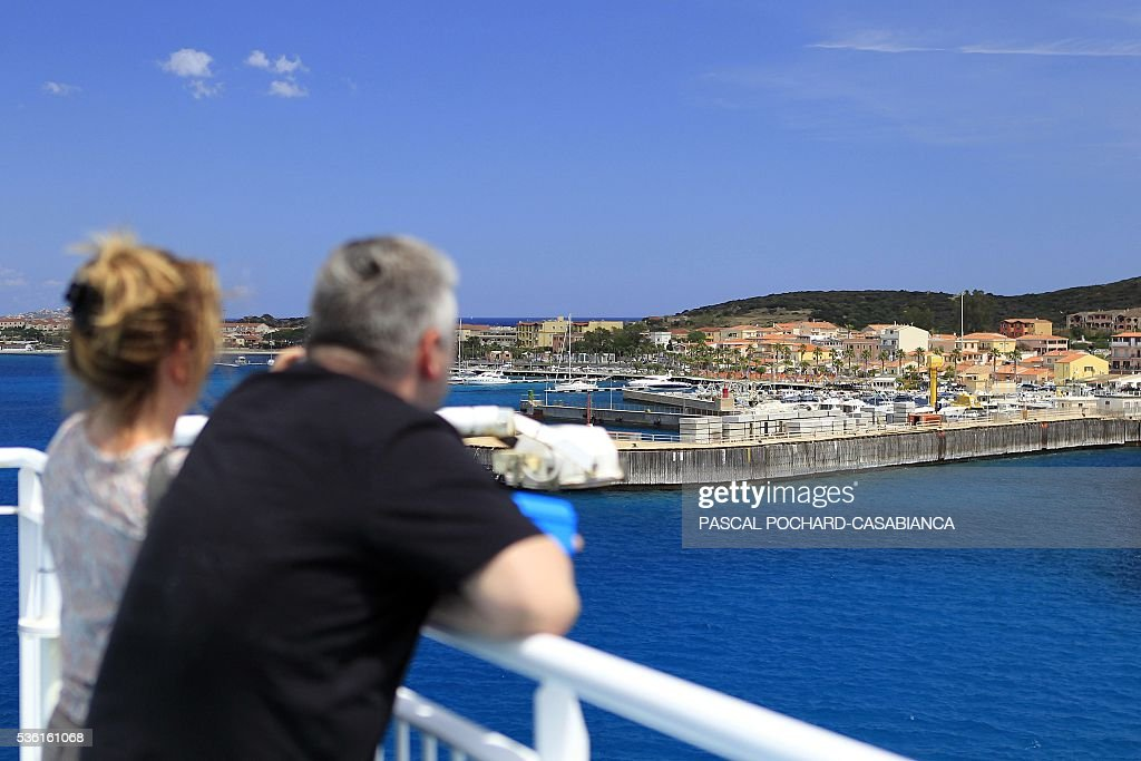 People stand on the deck of the new ferry boat Mega Andrea of the French Corsica Ferries company, on May 31, 2016 as they look to the harbour of Golfo Aranci on the Italian Mediterranean island of Sardegna. The Corsica Ferries opened, on May 31, a new line between Nice, Corsica and the island of Sardegna in Italy, reinforcing its position as a leader for the maritime transport between the two neighbour islands Corsica and Sardegna. / AFP / PASCAL