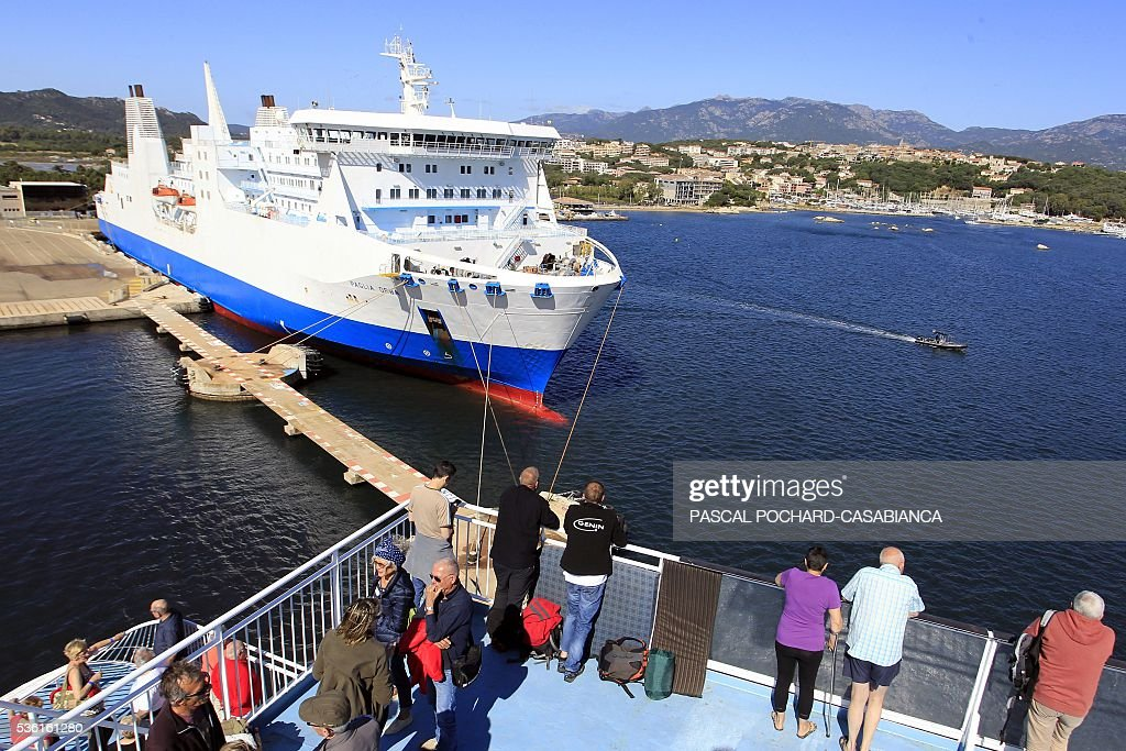 People stand on the deck of the new ferry boat Mega Andrea of the French Corsica Ferries company on May 31, 2016, in Porto-Vecchio on the French Mediterranean island of Corsica. The Corsica Ferries opened, on May 31, a new line between Nice, Corsica and the island of Sardegna in Italy, reinforcing its position as a leader for the maritime transport between the two neighbour islands Corsica and Sardegna. / AFP / PASCAL