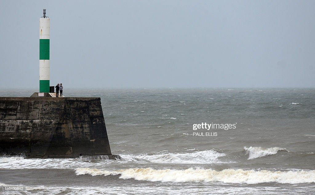 People stand on the end of the harbour breakwater at Aberystwyth in Wales on June 16, 2012 as bad weather continued to move in from the west. AFP PHOTO/PAUL ELLIS
