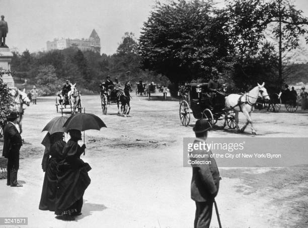 People stand on the mall and watch horsedrawn buggies travel down a dirt road in Central Park New York City