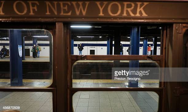 People stand on the platform as the Metropolitan Transit Authority 'Nostalgia' vintage subway train sits at the BroadwayLafayette station on December...