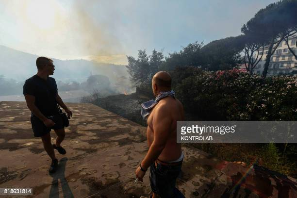 People stand on the roof of a house and look towards smoke on the horizon during a vast fire that threatened the inhabited areas between Naples and...