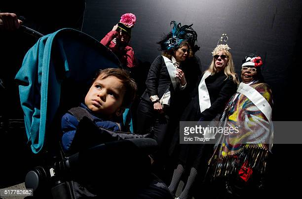 People stand on the sidewalk as a child rides by in a stroller during the Easter Parade and Bonnet Festival along 5th Avenue March 27 2016 in New...