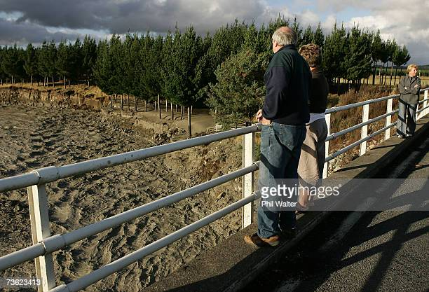 People stand on the Tangiwai Bridge and watch the Lahar as it makes its way along the path of the Whangaehu River after breaking the crater wall on...