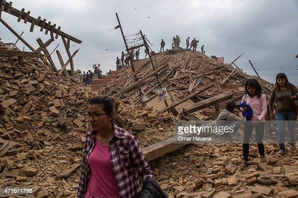 People stand on top of debris from a collapsed building at Basantapur Durbar Square watching the destruction following an earthquake on April 25 2015...