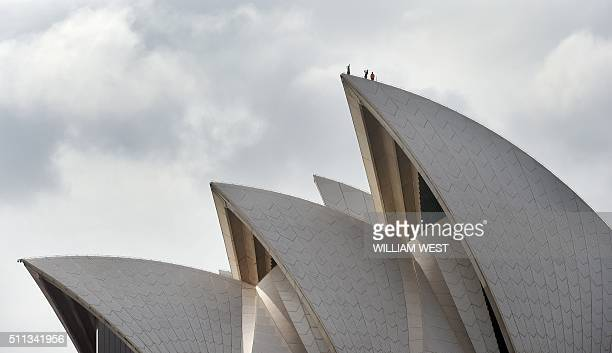 TOPSHOT People stand on top of one of the sails that make up the Sydney Opera House on February 20 2016 AFP PHOTO / William WEST / AFP / WILLIAM WEST