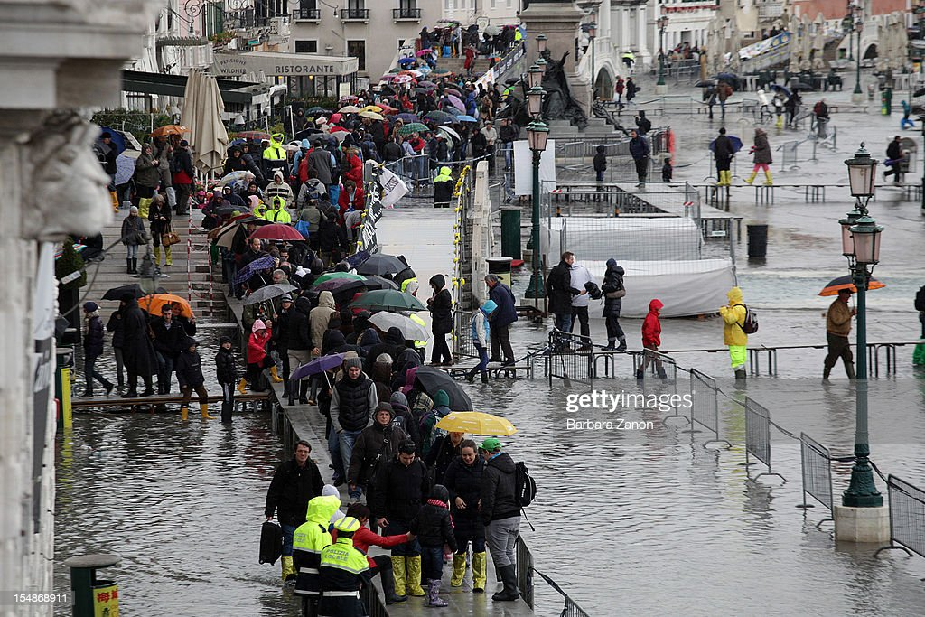People stand on walkways during high tide on the day of the Venice Marathon at Piazza San Marco on October 28, 2012 in Venice, Italy. The high tide or acqua alta stood at 123 centimeters this morning.