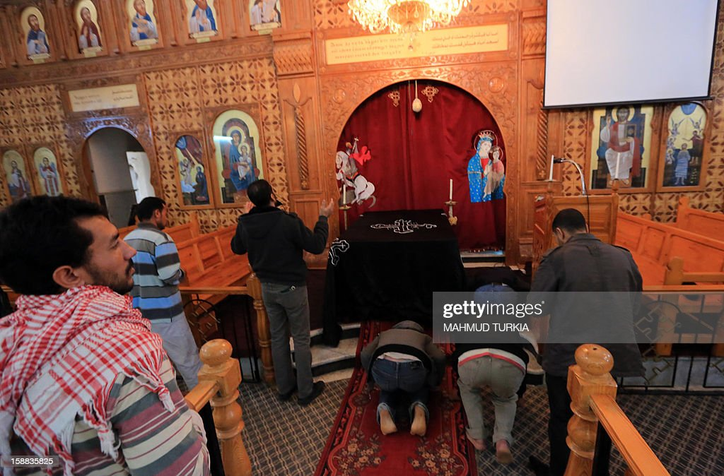 People stand ouside the Coptic church on December 31, 2012, damaged following an explosion last night in the Mediterranean town of Dafinya, just west of Misrata in which two Egyptians were killed. The stone church was built between 1936 and 1937 during Italian colonial rule and hundreds of Egyptians regularly attended services, the priest said.