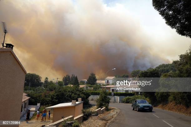 People stand outside a house in the courtyard and look at a the smoke coming from fire burning a forest on July 25 in Ortale de Biguglia near...