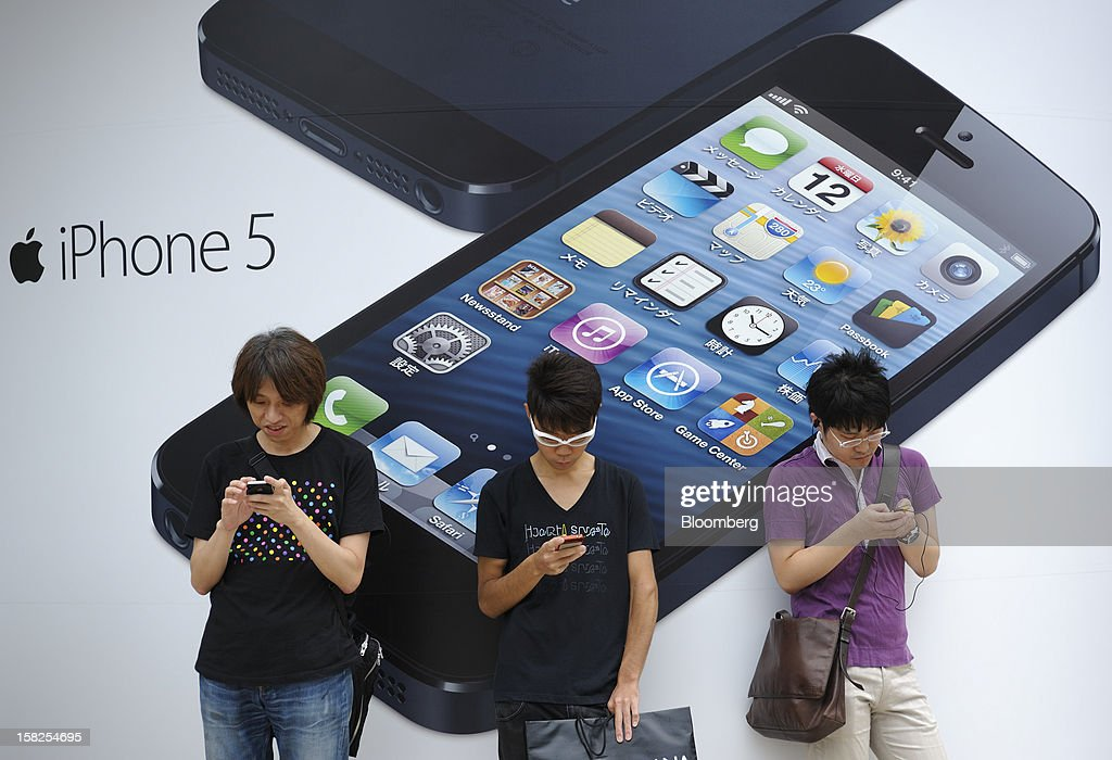 'BEST PHOTOS OF 2012' (): People stand outside a KDDI Corp. outlet prior to the launch of the Apple Inc. iPhone 5 in Tokyo, Japan, on Friday, September. 21, 2012. Apple is poised for a record iPhone 5 debut and may not be able to keep up with demand as customers lined up in Sydney, Tokyo and New York to pick up the latest model of its top-selling product. Photographer: Akio Kon/Bloomberg via Getty Images