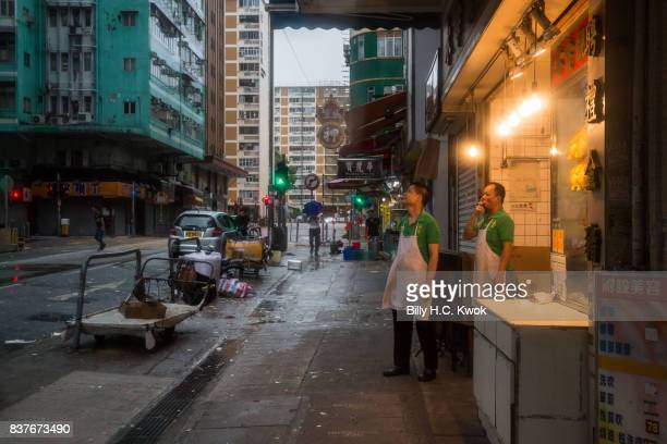 People stand outside a restaurant as typhoon Hato hits Hong Kong on August 23 2017 in Hong Kong Hong Kong Hong Kong's weather authorities raised...