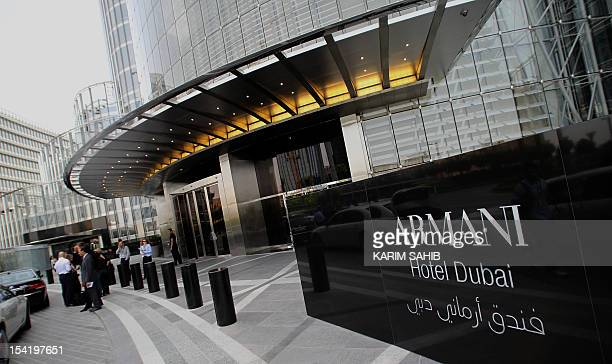 People stand outside Dubai's Armani hotel at the Gulf emirate's Burj Khalifa tower on April 27 2010 just before its glitzy opening ceremony The...