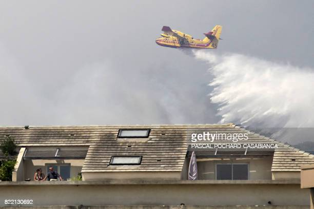 TOPSHOT People stand outside on a balcony as a Canadair aircraft drops water over a fire behind the building on July 25 in Ortale de Biguglia near...