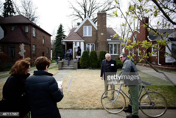 People stand outside one of twelve homes being auctioned off in the East English Village neighborhood April 27 2014 in Detroit Michigan The city of...