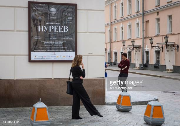 People stand outside the Bolshoi Theatre next to a plaque announcing the 'Nureyev' ballet premiere in Moscow on July 9 2017 Russia's Bolshoi theatre...