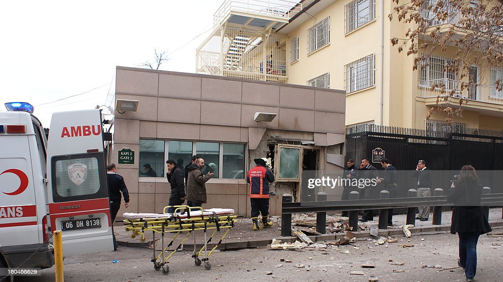 People stand outside the entrance of the US embassy in Ankara on February 1, 2013 after a blast killed two security guards and wounded several other people. It was not immediately known what caused the explosion but some media speculated it could have been a suicide bombing. The force of the blast damaged nearby buildings in the Cankaya neighbourhood where many other state institutions and embassies are also located.