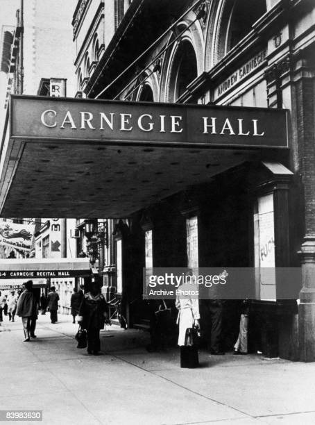 People stand outside the entrance to Carnegie Hall midtown Manhattan New York City circa 1980 Violinist Joseph Fuchs is appearing there according to...