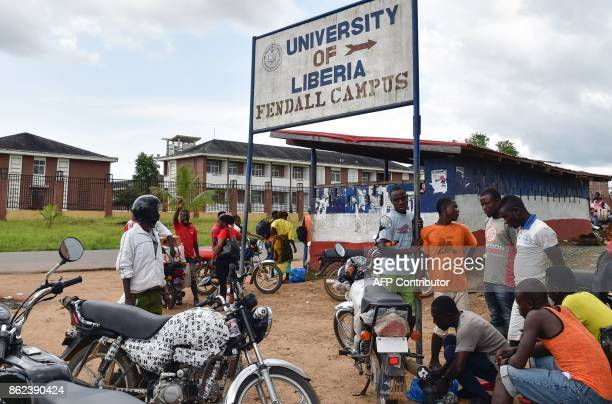 People stand outside the Fendall Campus of the University of Liberia near Monrovia on October 12 2017 / AFP PHOTO / ISSOUF SANOGO