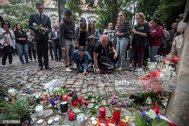 People stand outside the French Embassy where mourners left candles and flowers the day after the terror attack in Nice that has left at least 84...