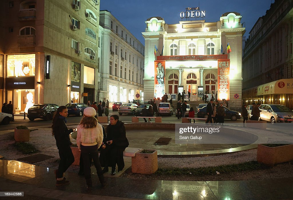 People stand outside the Odeon theatre on the night of a performance on March 8, 2013 in Bucharest, Romania. Both Romania and Bulgaria have been members of the European Union since 2007 and restrictions on their citizens' right to work within the EU are scheduled to end by the conclusion of this year. However, Germany's interior minister announced recently that he would veto the two countries' entry into the Schengen Agreement, which would not affect labour rights but would prevent passport-free travel.