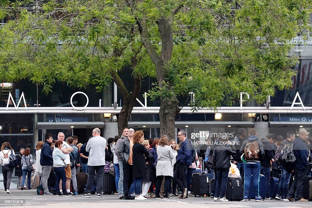 People stand outside the Paris-Montparnasse rail station as they wait for their delayed trains because the train traffic was suspended since this morning at the start and towards the Paris-Montparnasse rail station, due to a failure of traffic management system for the moment unexplained, according to France's national state-owned railway company SNCF.