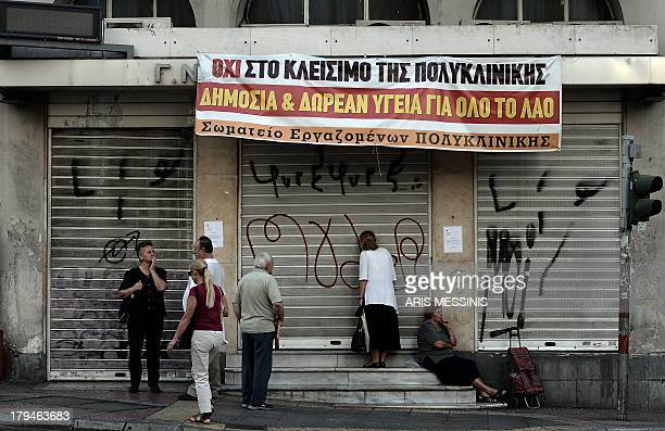 People stand outside the 'Polyklikini' one of the hospitals affected by overhaul of the health sector which has closed down for the time being with...