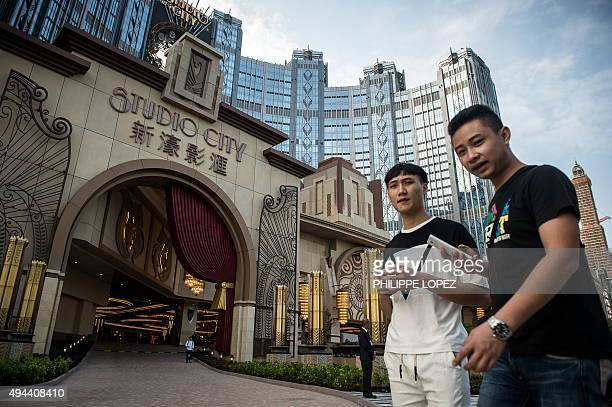 People stand outside the Studio City casino ahead of its opening in Macau on October 27 2015 Casino operator Melco Crown was to open its latest...