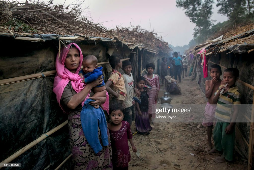 COX'S BAZAR, BANGLADESH - FEBRUARY 8: People stand outside their shelters in Kutapalong Rohingya refugee camp on February 8, 2017 in Cox's Bazar, Bangladesh. The United Nations estimates about 69,000 Rohingya Muslims have fled to Bangladesh from Myanmar since October last year after the Burmese army launched a campaign it calls 'clearance operations' in response to an attack on border police. Based on reports, Bangladesh plans to proceed with a controversial plan to relocate tens of thousands of Rohingya refugees from Myanmar to a remote island in Bay of Bengal, despite warnings it is uninhabitable and prone to flooding. Waves of Rohingya civilians have fled across the border since last year, most living in makeshift camps and refugee centers with harrowing stories on the Burmese army committing human-rights abuses, such as gang rape, arson and extrajudicial killing. The Rohingya, a mostly stateless Muslim group numbering about 1.1 million, are the majority in Rakhine state and smaller communities in Bangladesh, Thailand and Malaysia.