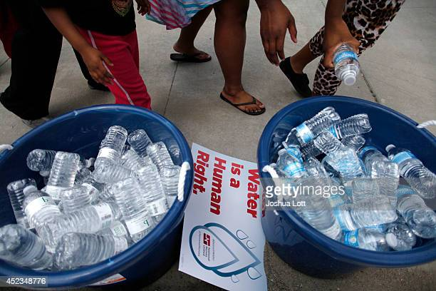 People stand over bottles of water as demonstrators protest against the Detroit Water and Sewer Department July 18 2014 in Detroit Michigan The...