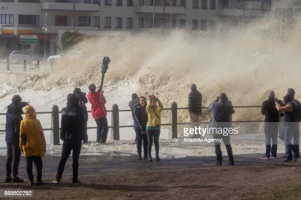 People stand over the bridge as the huge waves hit coastline during the heavy storm in Cape Town South Africa on June 7 2017